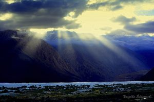The Bright sunny rays piercing from the clouds on the luscious green valley beneath.
